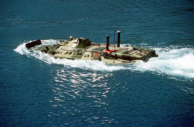 A BTR-80 swimming ashore from a tank landing ship